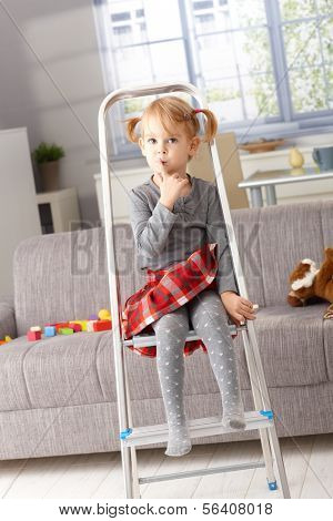 Cute little girl sitting impishly on ladder, putting forefinger on lips as calling for silence.