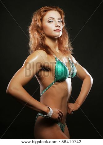A beautiful woman bodybuilder posing in green  bikini poster