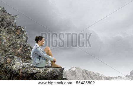 Image of young upset businesswoman sitting alone atop of mountain