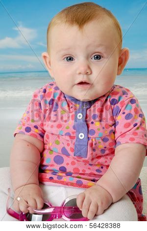 Sweet baby on vacation on beach with the sea in the background.