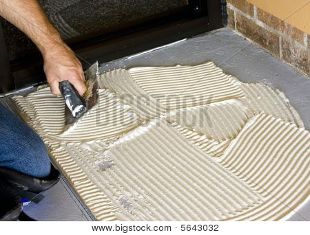 construction worker putting dowm mortar for floor tile poster