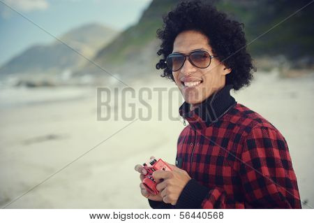 Happy hipster man smiling with toy camera at the beach