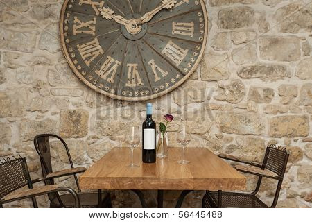 Wine bottle and two glasses on the wooden table decorated with rose.