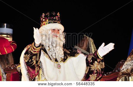 TARRAGONA, SPAIN - JANUARY 5: Melchior greet people during the Cavalcade of Magi on January 5, 2013 in Tarragona, Spain. The Magi and servants throw sweets to the children while parading in floats
