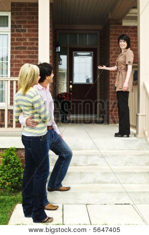 Pareja feliz con el agente de bienes raíces