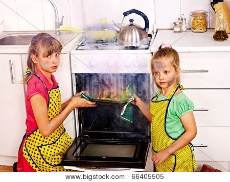 Children with  burned chicken cooking at kitchen.