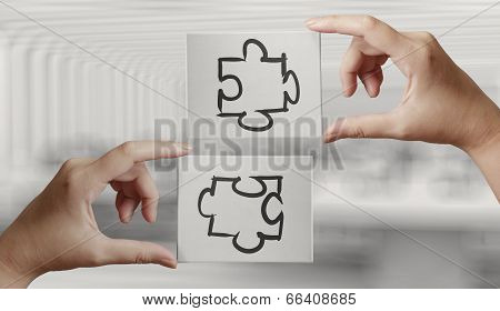 Hand Holding Hand Drawn  Partnership Puzzle Icon On Cavas Board As Concept