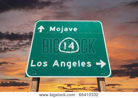 Mojave desert freeway sign towards Los Angeles with sunset sly.