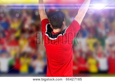 Excited football player cheering against blurry football pitch with crowd poster