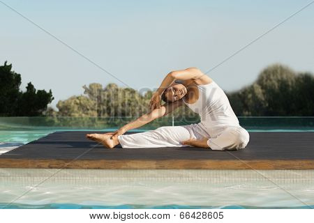 Peaceful brunette in janu sirsasana yoga pose poolside on a sunny day at the spa