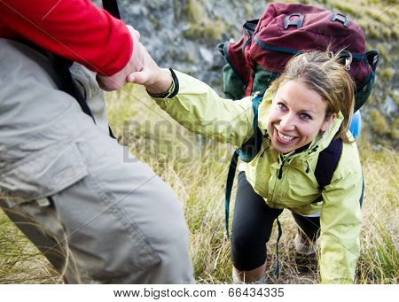 Hikers helping each other up a mountain.