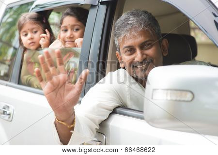 Indian family waving hands and saying goodbye, sitting in car ready to trip. Asian family lifestyle.