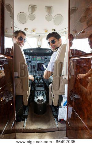 Portrait of confident pilot and copilot in cockpit of private jet