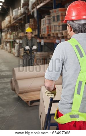Warehouse workers pushing handtruck stacked with rolled cardboard poster