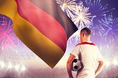 Football player holding the ball against fireworks exploding over football stadium poster