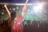 Excited asian football fan cheering against large football stadium with lights poster