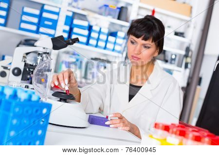 woman in a laboratory with microtube test tube  in hand and PCR centrifuge poster
