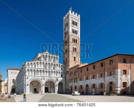 LUCCA, ITALY - June 30: Tourists at Church San Martino in Lucca Italy.People wait outside the Church Santa Maria Forisportam in Lucca Italy. They are huddled around a guide listening on June 30, 2014