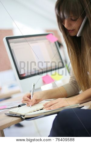 Young woman at work writing appointment in agenda