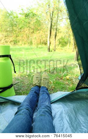 Legs lying in tourist tent in a forest