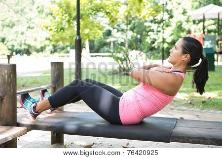 Beautiful woman doing sit ups on outdoor exercise park