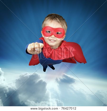 Superhero child flying above the clouds concept for childhood, imagination and aspirations