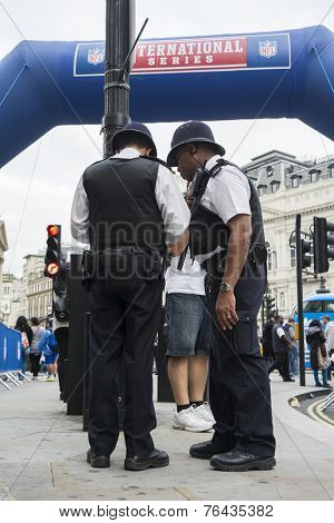 LONDON, UK - SEPTEMBER 27: British policemen standing next to inflatable NFL arch. September 27, 2014 in London. Regent street was closed to traffic to host NFL related games and events.
