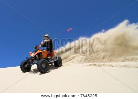Teen quad rider spraying sand in dunes