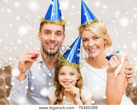celebration, family, holidays and birthday concept - happy family wearing blue party hats and blowing favor horns at home poster
