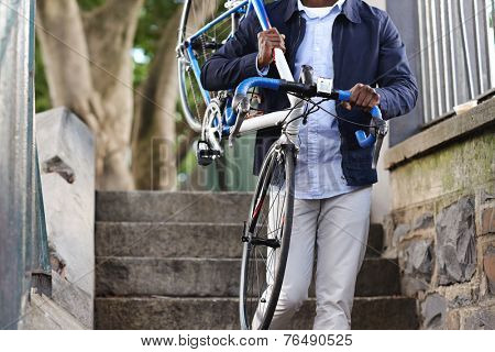 Man carrying bicycle down some stairs in city on his way to work