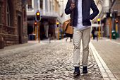 Young african man on vacation exploring european city cobblestone street poster
