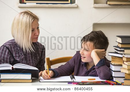 Tutor teaches a young student with his studies.