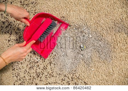 Broom, dirt on a carpet. A woman cleans the dust from carpets poster