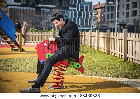 Young Man Reliving His Childhood Plying In A Children's Playground