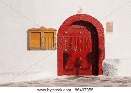 Red Wooden Door Of The Greek Monastery On The Island Of Mykonos.