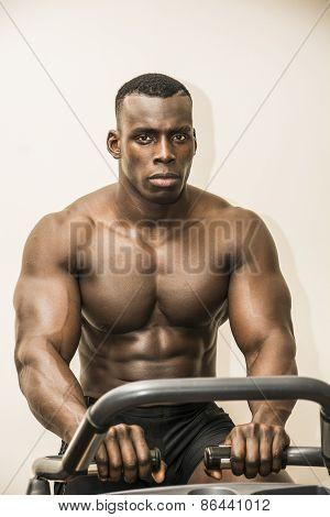 Muscular Black Bodybuilder Exercising On Stationary Bike In Gym