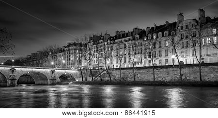 Seine River Quai de Bourbon on Ile Saint Louis with Pont Marie and evening lights. Black & White image of row of hotels particuliers in 4th arrondissement central Paris France poster