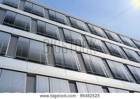 Facade of modern high-rise office building with covered windows Venetian blinds against blue sky poster