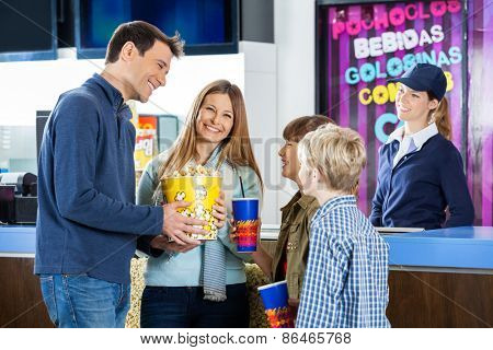 Happy family of four having snacks while female worker standing at cinema concession stand