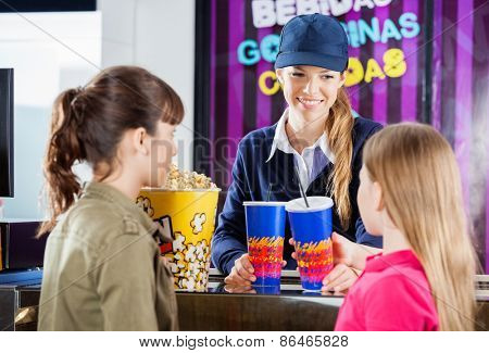 Female worker selling drinks and popcorn to girls at cinema concession counter
