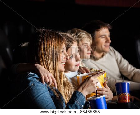 Family of four having snacks while watching movie in cinema theater