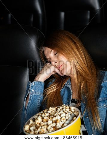 Bored woman with popcorn bucket sleeping at cinema theater