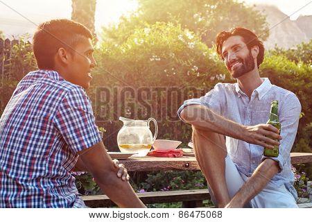 group of friends having outdoor garden dinner party with beer drinks