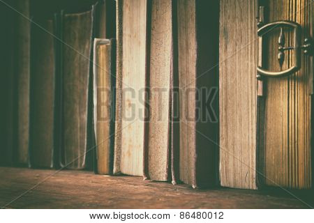detail of old books in wooden shelf.