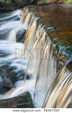 Motion Blurred Stream Falling Over A Weir