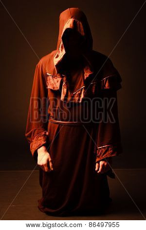 mysterious Catholic monk on dark background. studio shot poster