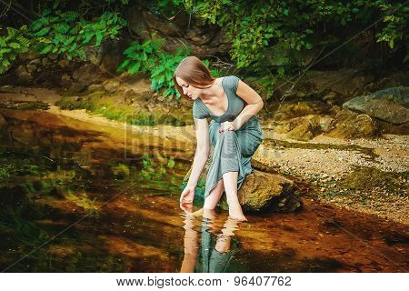 Woman sitting on the rock in a pond