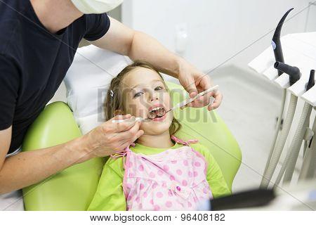 Little Girl Sitting On Dental Chair