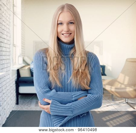 Happy blonde woman smiling arms crossed at stylish home.