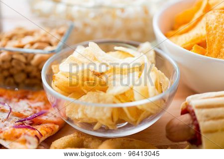 fast food, junk-food, cuisine and eating concept - close up of crunchy potato crisps in glass bowl and other snacks